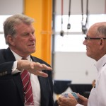 Governor Otter shows President Tom Harris how to palm a basketball, sans basketball.