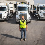 David Cummins, Heavy Haul Driver, stands in front of his truck.